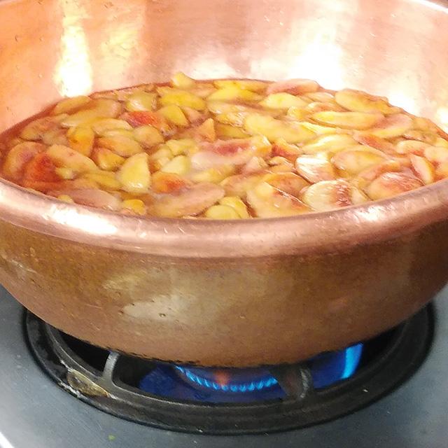 大きな銅鍋で弱火でグツグツと煮込まれる桃たち。